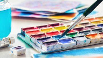 Set of watercolor paints, paintbrush, glass of water and paper sheets of watercolor paintings. Selective focus.